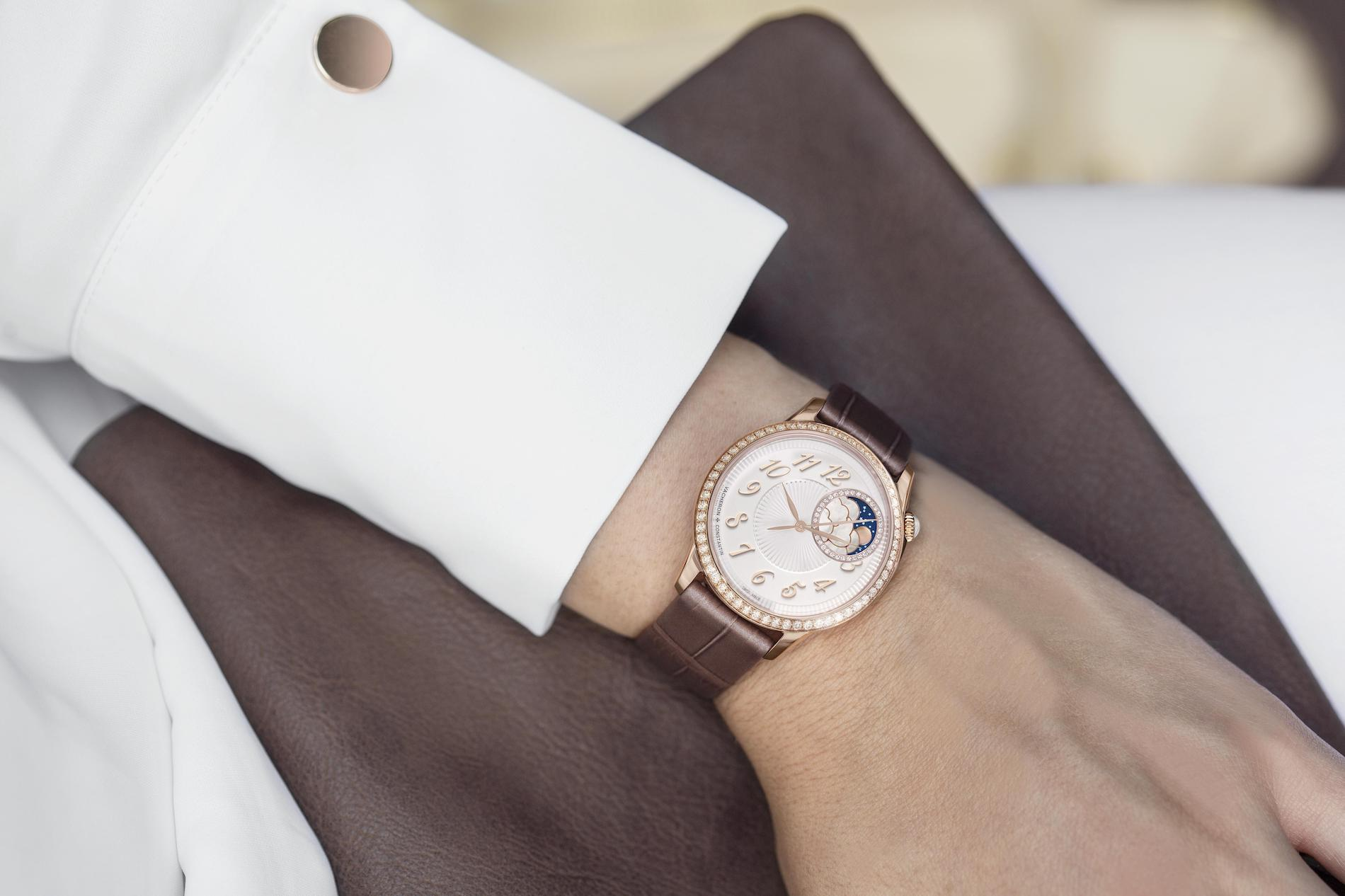 Vacheron Constantin Égérie moon phase timepiece in 18K 5N rose gold with a brown strap on the wrist of a woman.